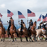 Cowgirls carring American flags at the Wilsall Rodeo. Montana