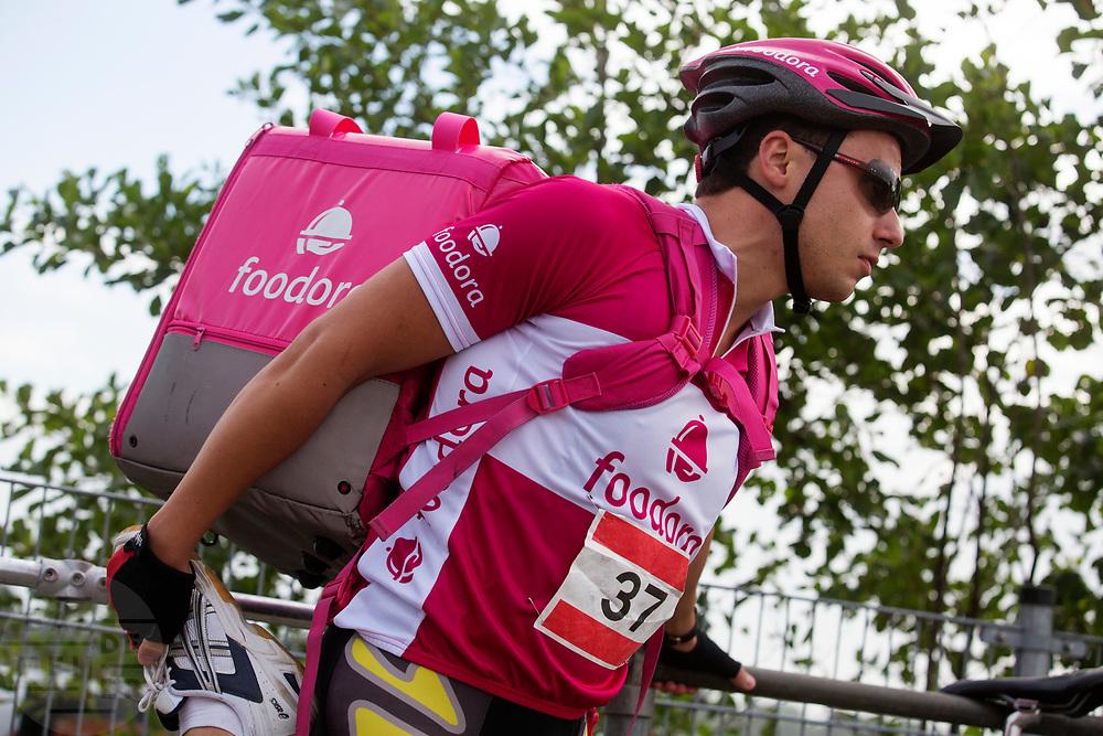 Een bezorger van Foodora doet wat strekoefeningen. In Nieuwegein wordt het NK Fietskoerieren gehouden. Fietskoeriers uit Nederland strijden om de titel door op een parcours het snelst zoveel mogelijk stempels te halen en lading weg te brengen. Daarbij moeten ze een slimme route kiezen.<br /> <br /> Stretching before the races. In Nieuwegein bike messengers battle for the Open Dutch Bicycle Messenger Championship.