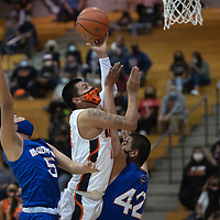 Gallup Bengal Jeffrey Yazzie (21) drives to the basket during a varsity basketball game against the Bloomfield Bobcats as Bobcats Aaron Watchman (5) and Ryan Thompson (42) defend Tuesday evening at Gallup High School in Gallup.