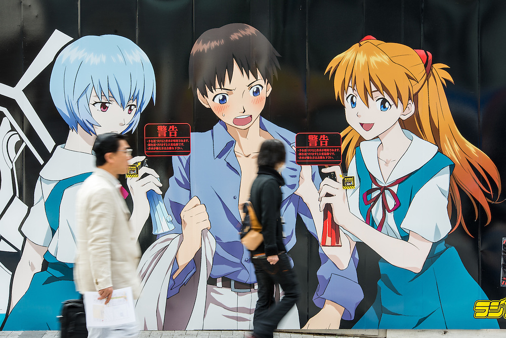 Pedestrians passing by a billboard using manga to advertise products in the Akihabara district of Tokyo.