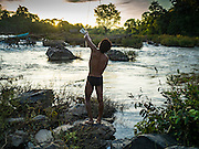 19 JUNE 2016 - DON KHONE, CHAMPASAK, LAOS: A fisherman prepares to use a hand over hand rope bridge to get across the Mekong River at Khon Pa Soi Waterfalls, on the east side of Don Khon. It's the smaller of the two waterfalls in Don Khon. Fishermen have constructed an elaborate system of rope bridges over the falls they use to get to the fish traps they set. Fishermen in the area are contending with lower yields and smaller fish, threatening their way of life. The Mekong River is one of the most biodiverse and productive rivers on Earth. It is a global hotspot for freshwater fishes: over 1,000 species have been recorded there, second only to the Amazon. The Mekong River is also the most productive inland fishery in the world. The total harvest of fish from the Mekong is approximately 2.5 million metric tons per year. By some estimates the harvest in the Tonle Sap (in Cambodia) had doubled from 1940 to 1995, but the number of people fishing the in the lake has quadrupled, so the harvest per person is cut in half. There is evidence of over fishing in the Mekong - populations of large fish have shrunk and fishermen are bringing in smaller and smaller fish.     PHOTO BY JACK KURTZ