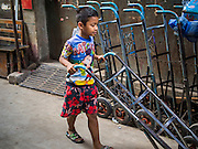 21 OCTOBER 2014 - BANGKOK, THAILAND:  A boy pushes a handtruck through the Pak Khlong Talat market on the Chao Phraya River in Bangkok.   PHOTO BY JACK KURTZ