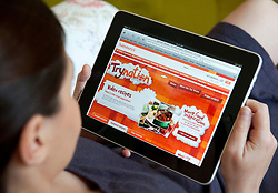 Woman shopping at online Sainsbury's store using an iPad tablet computer