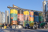 Concrete silos at Ocean Concrete on Granville Island in Vancouver, Britsh Columbia, Canada.  Ocean Concrete is Granville Island's oldest tenant and the colourful silos were spay painted by Brazilian artist OSGEMOEOS for the Vancouver Biennale in 2015.