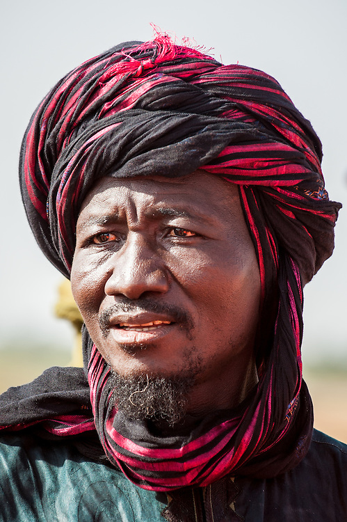 Stock photograph of an Fulani chief wearing his traditional colourful robes in northern Burkina Faso. The Fulani or Peul are nomadic herdsmen of the Sahel region of West Africa.