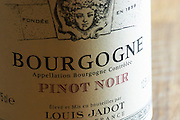 Closeup close-up of a wine bottle label Maison Louis Jadot Bourgogne Pinot Noir Appellation Bourgogne Controlee with the Baccus Bacchus symbol of the producer founded in 1859, Maison Louis Jadot, Beaune Côte Cote d Or Bourgogne Burgundy Burgundian France French Europe European