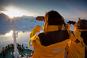 Tourists view the sunset on board the Scandinavian-built ice-breaker Akademik Sergey Vavilov, originally built for the Russian Academy of Science and still used occasionally by scientists, is now predominantly used for adventure touring in both the Arctic and the Antarctic. The ship is currently operated by a Russian crew, and staffed with employees of the adventure touring company Quark Expeditions, and carries around 100 passengers at a time. .
