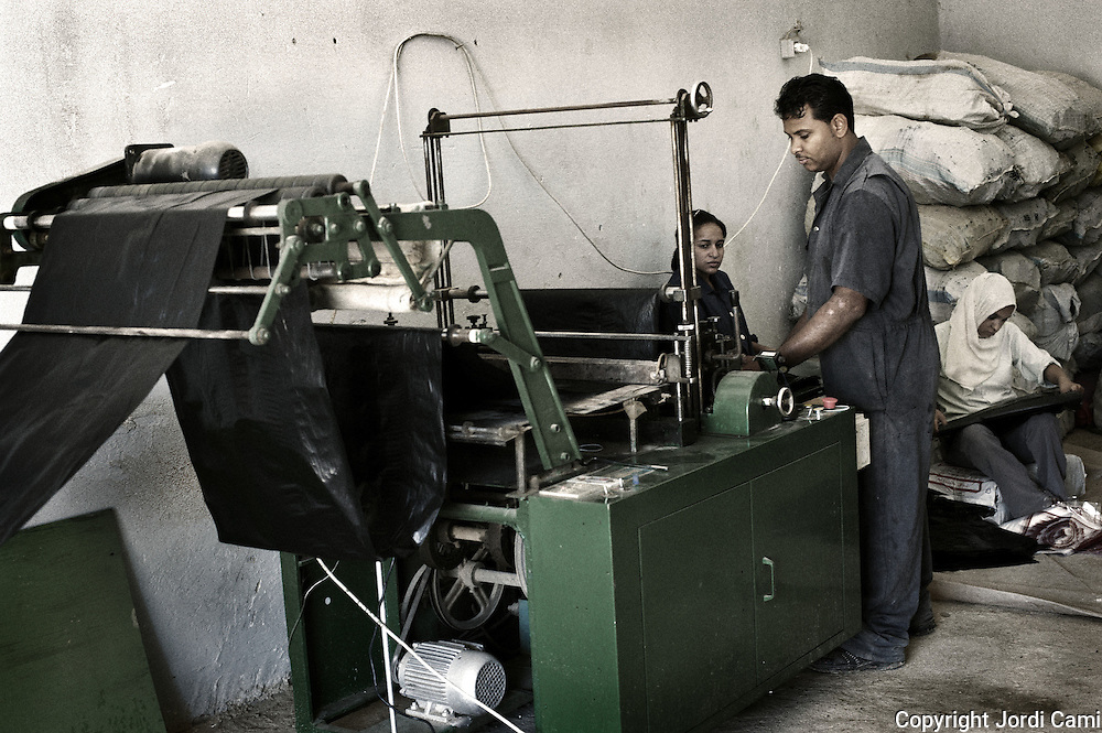 """Zabbaleen workers in one of the machines that produce garbage bags with recycled plastic at the recycling plant Katameya, who heads the NGO APE on the outskirts of Cairo. In the middle of Manshiet Nasr a Cairo neighborhood is located Mokattam settlement known as """"Garbage City"""" is inhabited by Zabbaleen, a community of about 45,000 Coptic Christians living for decades to recycle waste generated by the Egyptian capital: plastic, aluminum, paper and organic waste transformed into compost. Most part of the Association for the Protection of the Environment (APE), an NGO that works in the area, whose objectives are to protect the environment and improve the livelihoods of garbage scavengers in Cairo. According to the UN, the work is done in Mokattam is one of the ten best examples of world environmental improvement. El Cairo , Egipt, June 2011. ( Photo by  Jordi Camí )."""