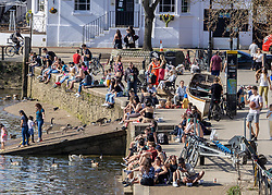© Licensed to London News Pictures. 30/03/2021. London, UK. Sunbathers and picnickers enjoy the sunshine in a busy Richmond riverside, South West London as weather forecasters predict the hottest March in over 50 years with highs of 23c in the South East today. From yesterday, two households or six people are now allowed to meet up marking the end of the Stay at Home advice. Playing golf, tennis and organised outdoor sports is also allowed as England starts to unlock after a year of Covid-19 restrictions. Photo credit: Alex Lentati/LNP