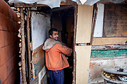 Ivan (26) getting home after cutting wood to be able to heat the little hut where he is living with his family at the Roma settlement in Ostrovany.