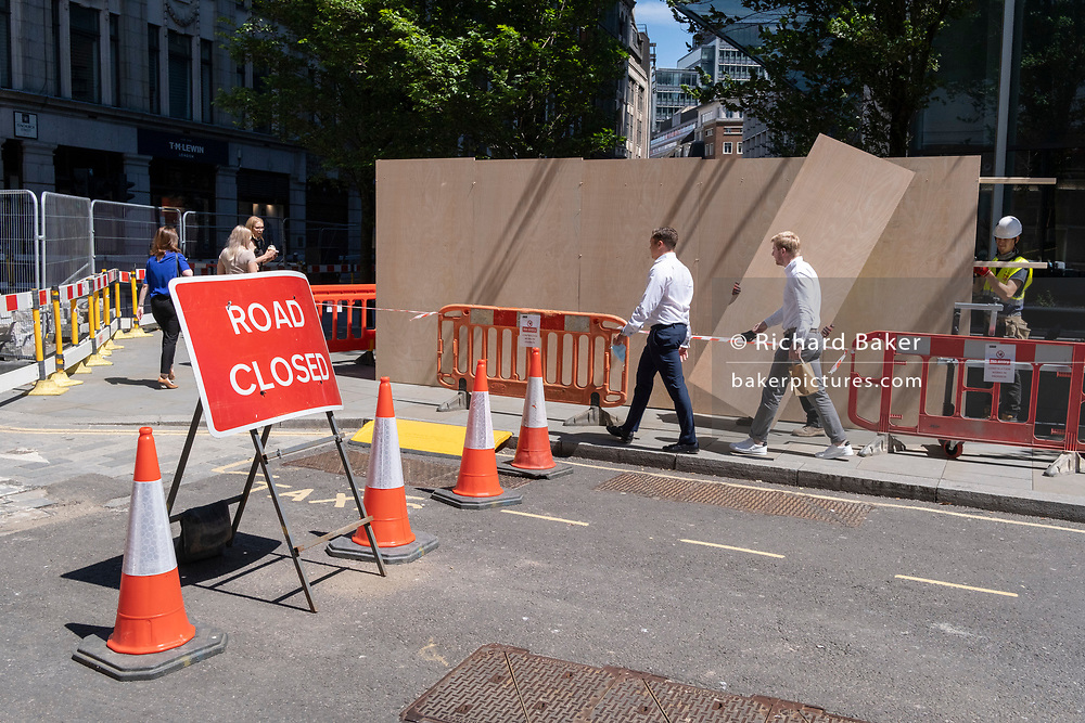 City workers walk past a new plyboard construction hoarding in the City of London, the capital's financial district, on 8th June 2021, in London, England.