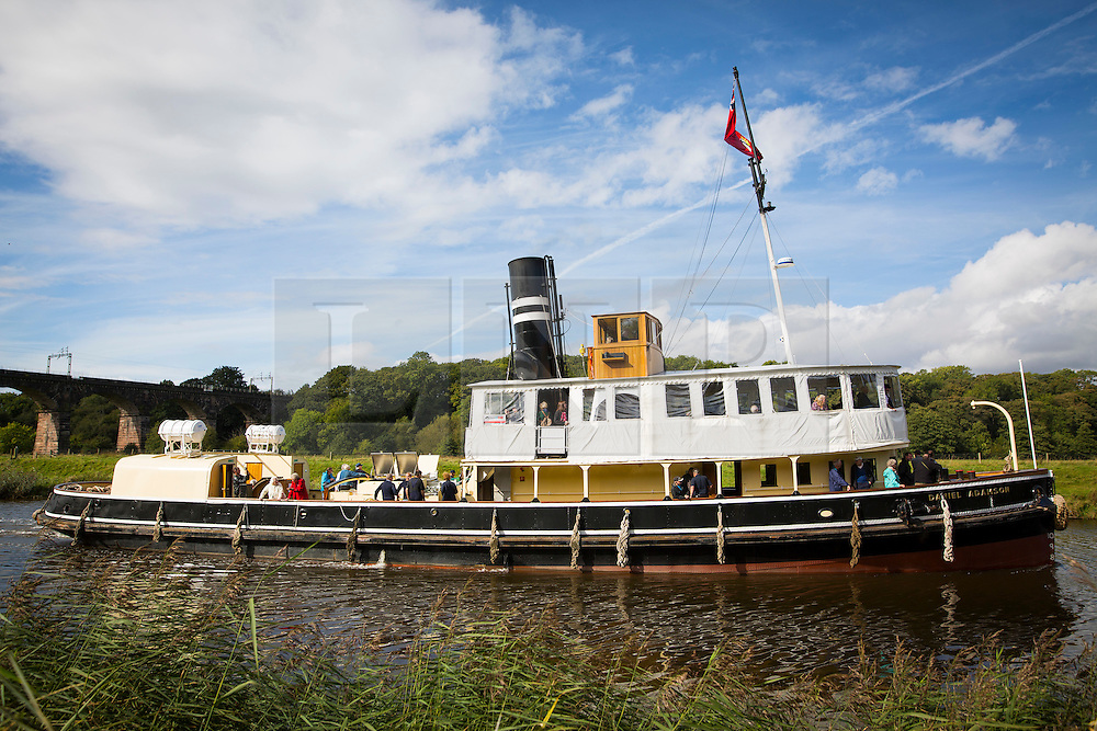 """© Licensed to London News Pictures. 30/09/2016. Bartington UK. Picture shows the Daniel Adamson making it's way along the River Weaver on it's maiden voyage after a £5M renovation. The Daniel Adamson steam boat has been bought back to operational service after a £5M restoration. The coal fired steam tug is the last surviving steam powered tug built on the Mersey and is believed to be the oldest operational Mersey built ship in the world. The """"Danny"""" (originally named the Ralph Brocklebank) was built at Camel Laird ship yard in Birkenhead & launched in 1903. She worked the canal's & carried passengers across the Mersey & during WW1 had a stint working for the Royal Navy in Liverpool. The """"Danny"""" was refitted in the 30's in an art deco style. Withdrawn from service in 1984 by 2014 she was due for scrapping until Mersey tug skipper Dan Cross bought her for £1 and the campaign to save her was underway. Photo credit: Andrew McCaren/LNP"""