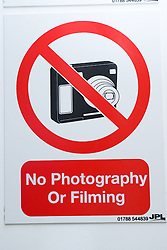 Notice on door warning that no photography is permitted in the area,