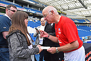 Tommy Charlton of England over 60's signs his autograph for a girl after the match during the world's first Walking Football International match between England and Italy at the American Express Community Stadium, Brighton and Hove, England on 13 May 2018. Picture by Graham Hunt.