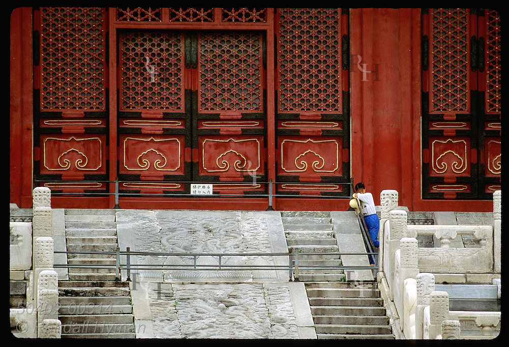 Ornate red doorway & large stone fresco dwarf woman groundskeeper in the Forbidden City; Beijing. China