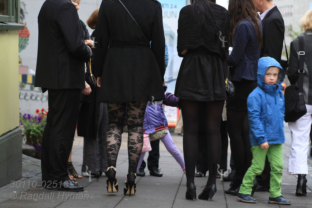 Young children wait on sidewalk with stylishly-dressed adults late on a summer night in downtown Reykjavik, Iceland.