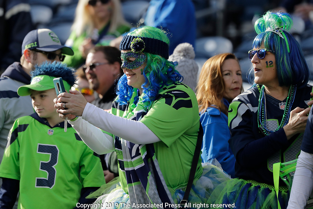 Seattle Seahawks fans watch as players warm up before an NFL football game against the Tampa Bay Buccaneers, Sunday, Nov. 3, 2019, in Seattle. (AP Photo/John Froschauer)
