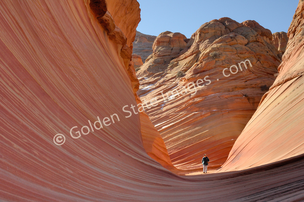 """A hiker is dwarfed by the breaking wave frozen in rock.<br /> <br /> Paria Canyon - Vermillion Cliffs Wilderness area in Southern Utah.<br /> <br /> Coyote Buttes North located in the Paria Canyon - Vermilion Cliffs Wilderness. This area features one of the most well-known geologic sandstone formations in the world, called """"The Wave"""".<br /> <br /> The Wave is a spectacular area of sandstone formations twisted into the shapes of breaking waves pillars cones and mushrooms.<br /> <br /> An ancient sea laid down layers of sediment deposits which hardened to form the multicolored sandstone rock. Over eons the actions of water the cycles of baking heat and subfreezing temperatures and wind have formed its complex undulating shapes.<br /> <br /> The deep reds of the rock and their shapes appear to change with the seasons and time of day."""