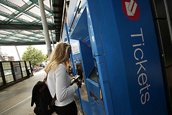 File photo dated 19/08/14 of a woman buying a train ticket from a machine at Finsbury Park station in north London, as rail passengers planning to travel over the Christmas period are being urged to buy tickets now to save money.
