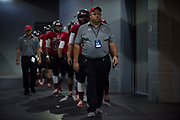 Iraan High School football head coach Mike Kirchhoff leads the team to the field before the state championship game at AT&T Stadium in Arlington, Texas on December 15, 2016. (Cooper Neill for The New York Times)