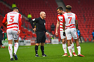 Referee Andy Woolmer speaks to a group of Doncaster players during the EFL Sky Bet League 1 match between Doncaster Rovers and Scunthorpe United at the Keepmoat Stadium, Doncaster, England on 15 December 2018.