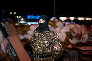 """Portrait of a man with uniform and mask who came for a nightshift to protect the barrikades which are blockading a building supplies store named """"Epicenter"""" in the city of Lviv, Ukraine."""