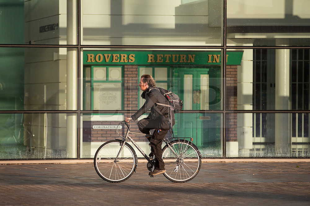 © Licensed to London News Pictures . 24/09/2014 . Media City , Salford , UK . A man on a bicycle passes a mock up of the front of the Rovers Return Inn . Autumn sunshine and big reflected light off the surface of glass buildings at Salford's Media City this morning as commuters travel to work  . Photo credit : Joel Goodman/LNP