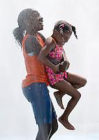 WATERBURY, CT- 30 JULY 06- 073006JT10-.Irazjah Richardson, 12, carries her cousin Kourtne Johnson, 5, through the sprinkler at Chase Park in Waterbury on Sunday..Josalee Thrift Republican-American