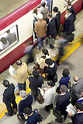 overhead view of commuters entering train Tokyo Japan