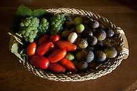 a basket of foods in Italy- tomatoes, figs, eggs, grapes