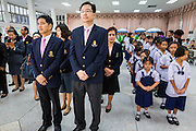 09 OCTOBER 2014 - BANGKOK, THAILAND: Businessmen and school children line up in the lobby at Siriraj Hospital to sign cards for Bhumibol Adulyadej, the King of Thailand. The King has been hospitalized since Oct. 4 and underwent emergency gall bladder removal surgery Oct. 5. The King is also known as Rama IX, because he is the ninth monarch of the Chakri Dynasty. He has reigned since June 9, 1946 and is the world's longest-serving current head of state and the longest-reigning monarch in Thai history, serving for more than 68 years. He is revered by the Thai people and anytime he goes into the hospital thousands of people come to the hospital to sign get well cards.   PHOTO BY JACK KURTZ