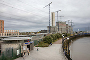 Commuters exit from Canning Town underground station with the Thames River and heavy building construction in the background on the 31st August 2019 in East London in the United Kingdom.