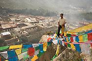 A man hangs Tibetan prayer flags during a religious festival at Drepung Monastery in Lhasa, Tibet.