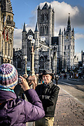 A couple is having their picture at the Sint michael's Brighe in Ghent with the famous 3 towers of Sint Nicolaschurch, Belfry and Sint Baafscathedral