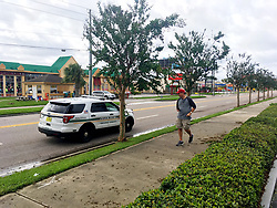 """An Orange County Sheriff's deputy stops a tourist on International Drive and tells him to go back to his hotel. On loudspeaker, one said, """"You can be arrested. There are downed power lines. It's still dangerous."""" Photo by Orlando Sentinel/TNS/ABACAPRESS.COM"""