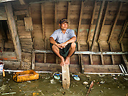 04 NOVEMBER 2015 - YANGON, MYANMAR: A man waits out a passing rain storm underneath the hull of an overturned small wooden ferry on the banks of the Yangon River in Dala. Dala is located on the southern bank of Yangon River across from downtown Yangon, Myanmar. Many Burmese live in Dala and surrounding communities and go across the river into central Yangon for work. Before World War 2, the Irrawaddy Flotilla Company had its main shipyards in Dala. That tradition lives on in the small repair businesses the work on the hundreds of small wooden boats that serve as commuter ferries for the people of Yangon. The boats are pulled up onto the riverbank in Dala and repaired by hand.    PHOTO BY JACK KURTZ