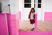 A young girl stands on a pink porch along a street in Santa Rosalia, Baja California Sur, Mexico on January 26, 2009.