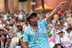 © Licensed to London News Pictures. 05/01/2014. An Anti-Governement protestor blows her whistle at a Rally during the third day of the 'Bangkok Shutdown' as anti-government protesters continue with their 'shutdown' of Bangkok.  Major intersections in the heart of the city have been blocked in their campaign to oust Prime Minister Yingluck Shinawatra and her government in Bangkok, Thailand. Photo credit : Asanka Brendon Ratnayake/LNP