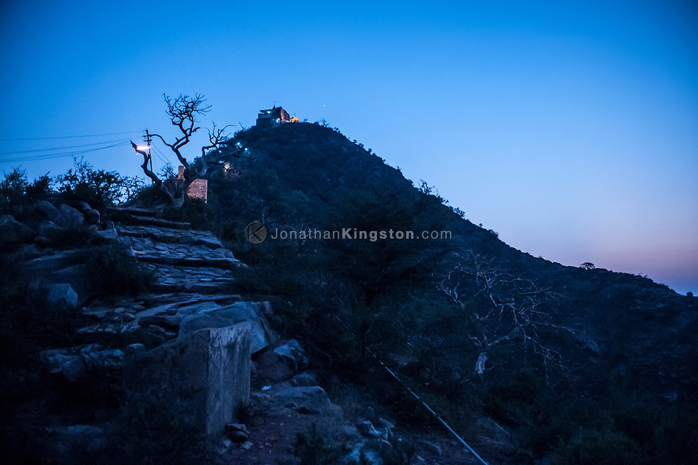 Evening light illuminates a small temple on a hill near Pushkar, India.