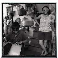 In a house close from the railway of Hanoi, a man repares a plastic bowl while his wife stands beside him and smile to him. Interior of the house is quite small and quite a mess.