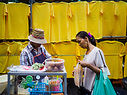 03 JULY 2018 - BANGKOK, THAILAND: A Thai crepe seller prepares a woman's order in front of a shop selling yellow tee shirts to honor the King of Thailand. The birthday of King Maha Vajiralongkorn Bodindradebayavarangkun, Rama X, is 28 July. The King, the only son of Thailand's late King Bhumibol Adulyadej, became the King of Thailand in 2016 after the death of his father. King Vajiralongkorn was born on 28 July 1952, a Monday. In Thai culture each day of the week has a color, and yellow is the color is associated with Monday, so people wear yellow for the month before his birthday to honor His Majesty.     PHOTO BY JACK KURTZ
