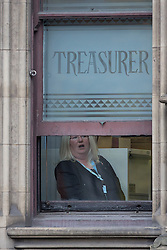 "© Licensed to London News Pictures . 23/10/2015 . Manchester , UK . A woman inside Manchester Town Hall by windows with "" TREASURER "" stencilled , as Chinese president , Xi Jinping , visits inside as part of his state visit to the United Kingdom . Photo credit: Joel Goodman/LNP"