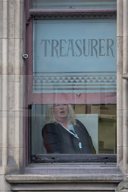 """© Licensed to London News Pictures . 23/10/2015 . Manchester , UK . A woman inside Manchester Town Hall by windows with """" TREASURER """" stencilled , as Chinese president , Xi Jinping , visits inside as part of his state visit to the United Kingdom . Photo credit: Joel Goodman/LNP"""