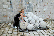 Child (9 years old) leaning on pile of pseudo-cannonballs, Fortress Lovrinjenac (Fort of Saint Lawrence), Dubrovnik old town, Croatia