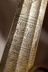 """© Licensed to London News Pictures. 23/03/2017. London, UK. A technician examines a Scottish basket-hilted broadsword, said to be that carried by Alexander, 4th Lord Forbes of Pitsligo (Est. GBP1,200-1,500).  The inscription near the hilt reads """"Prosperity to SchotLand and no union"""".  Preview at Sotheby's New Bond Street of property from two great Scottish families, the Forbeses of Pitsligo and the Marquesses of Lothian, which will be auctioned in London on 28 March.   Photo credit : Stephen Chung/LNP"""