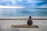 A man sits on the beach on the tiny island of Gili Air, Indonesia.