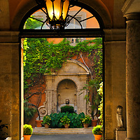 Rome. Lazio. Italy. View through the arched doorway entrance of the Embassy of the Kingdom of Spain. The entrance was built by Francesco Borromini, and past the entrance one can see a charming garden and fountain in the embassy's pretty courtyard.