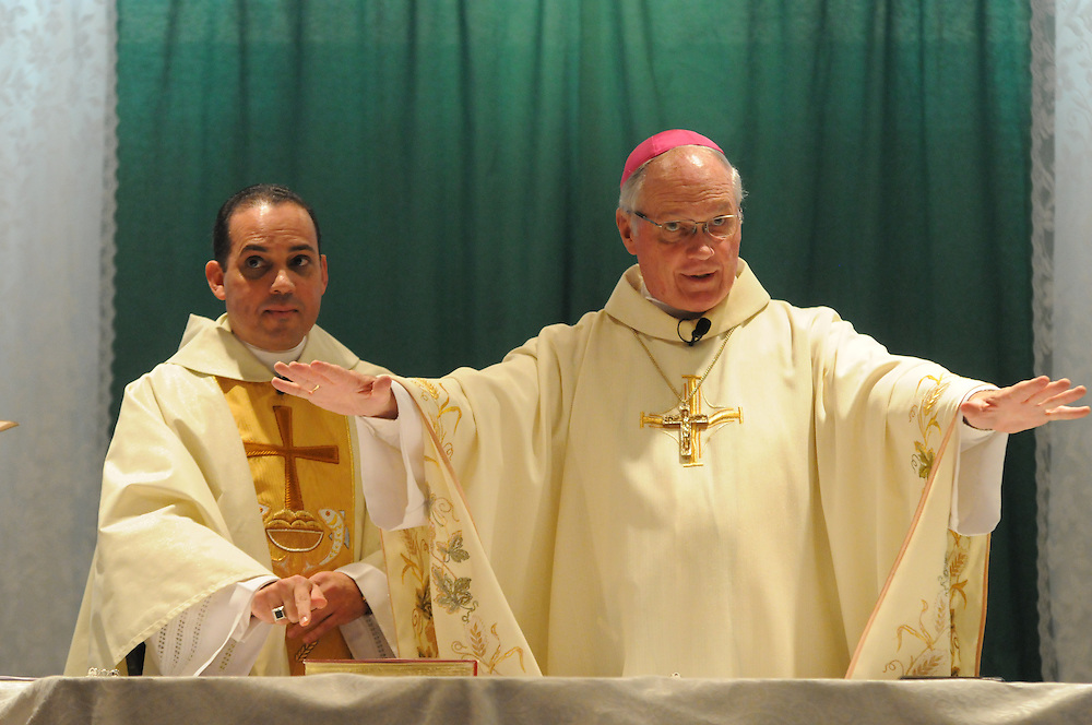 Bishop George Rassas (R) leads an installation mass for Fr. Claudio Diaz (L) at Mision San Juan Diego in Arlington Heights.