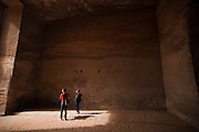 Tourists stand inside the cavernous interior of The Monastery (Al Deir) in Petra, Jordan.