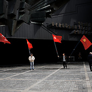Ukrainian men holding flags of the communist party, attend a ceremony that marks 69 years since the Soviets defeated the Nazis, at the War Memorial in central Donetsk, amid tensions over the referendum for autonomy of the region to be held over the weekend.